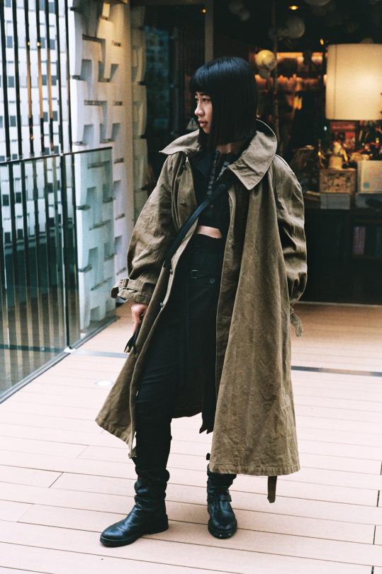 La longueur du manteau, déboutonné, contraste avec la taille haute du pantalon, permettant d'accentuer encore plus l'effet d'une longueur de jambes démesurées.