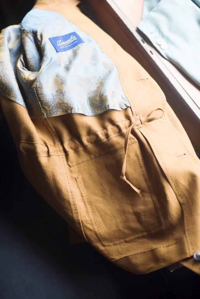 Un cordon de serrage se présente de cette manière, il est donc toujours possible d'ajuster le cintrage de la veste à ce niveau. Comparé à une ceinture, cela permet de conserver une ligne plus dépouillé ce qui peut être utile si la veste est assez chargée visuellement (nombre et forme des poches, présences de motifs…).