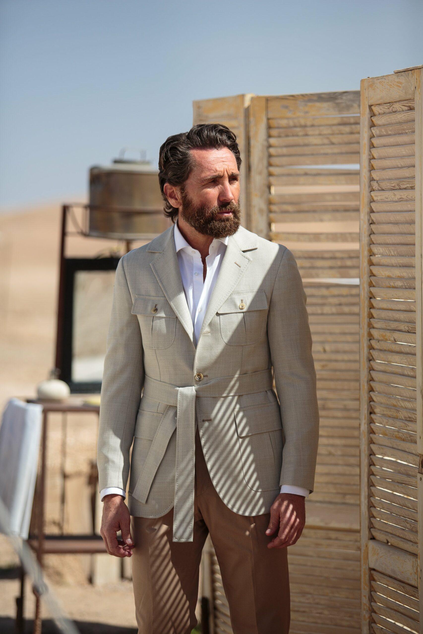Les revers sont quasiment identiques à ce que l'on peut trouver sur une veste sport classique. Les basques sont arrondis, les quartiers ouverts pour un esprit sportif. De façon cohérente avec cet esprit sportif, les poches sont plaquées avec soufflets et rabats y compris au niveau de la poitrine. La ceinture nouée permet de souligner la taille et de conférer une allure décontractée permettant de ne pas sembler sur-habillé.  Source : Pini Parma.