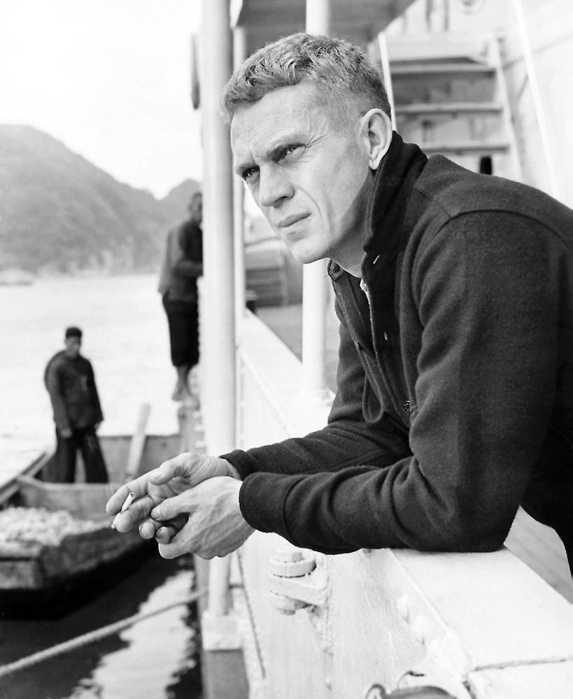 Steve McQueen portant une chemise CPO ; on devine en dessous un col, qui pourrait être celui d'un pull Aran beige crème.