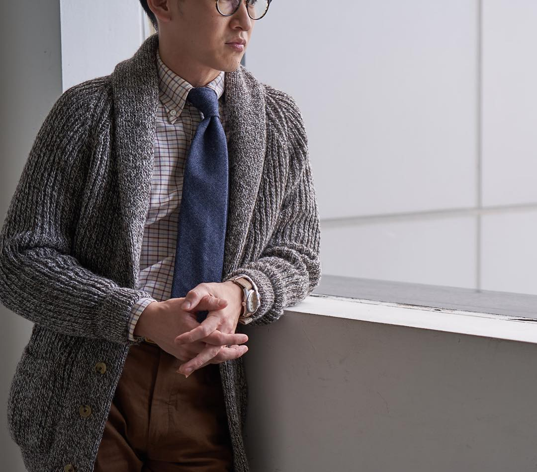 """Ici, une chemise à col boutonné à motif tattersall associée à un cardigan en maille épaisse. Celui-ci remplace admirablement une veste sport dans cette tenue des plus confortables pour l'hiver. Source : Vanda Fine Clothing. <a href=""""https://www.sartorialisme.com/le-cardigan/""""> À ce propos, vous pouvez lire notre article sur le cardigan</a>"""