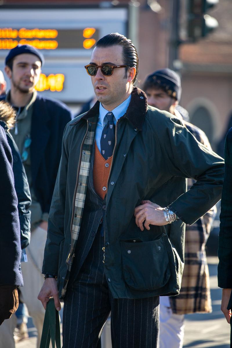 La rayure est franche et donc de mauvais goût (il suffisait de regarder Alan Flusser pour s'en convaincre). La barbour jure avec le costume car d'une part la teinte n'est pas bonne, mais surtout le costume n'est pas assez décontracté pour être porté facilement avec la barbour. Vient ensuite l'écoeurant mélange de l'orange vif du cardigan, du bleu vif de la chemise et de la cravate de mauvais goût (de façon générale: blasons sur une cravate ou une veste = plouc).