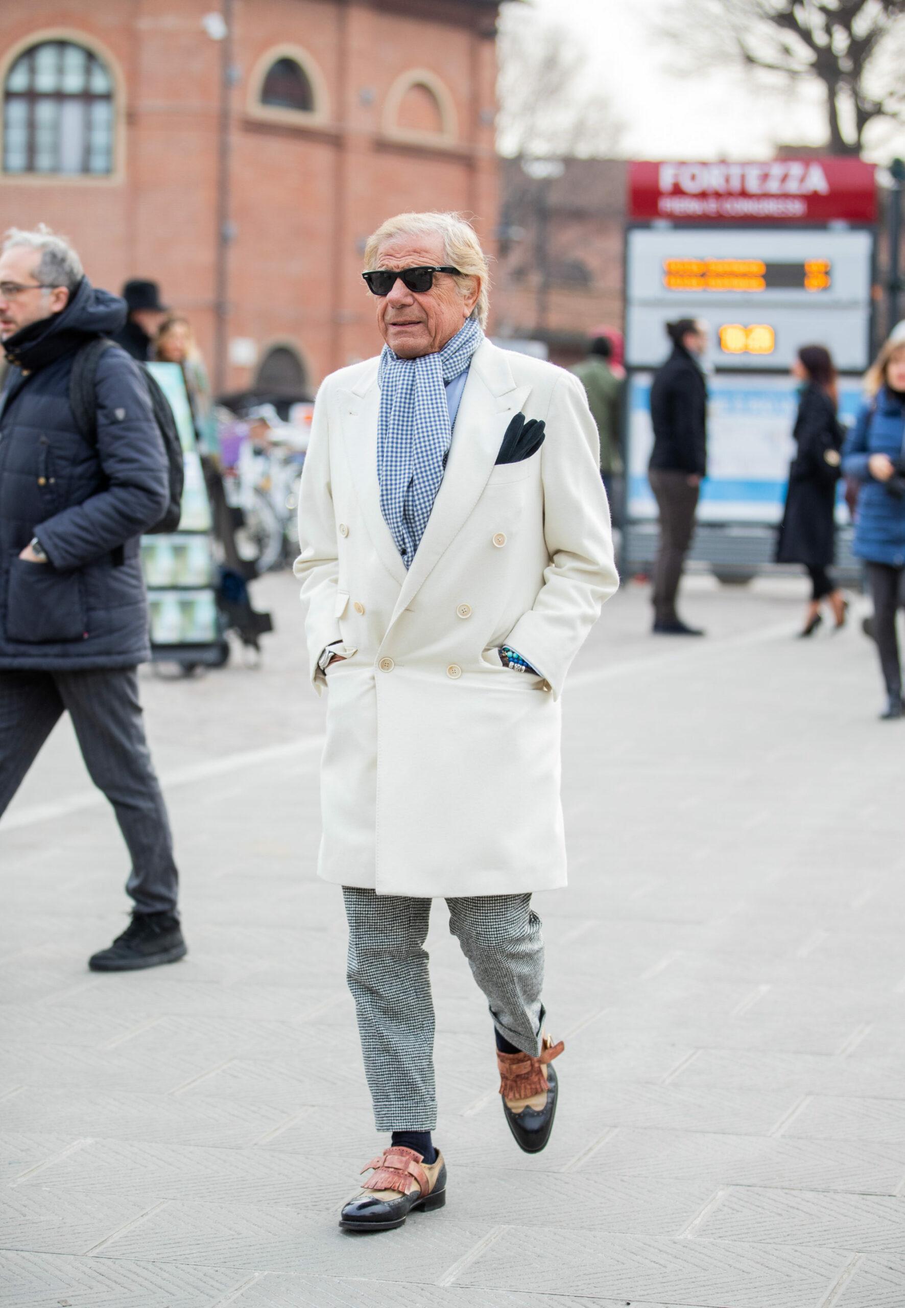 L'idole des ploucs: le manteau blanc, la pochette assortie aux lunettes de soleil. Au moins, l'écharpe façon cochonou-vichy nous évite la vue d'une cravate brodée d'un 7.