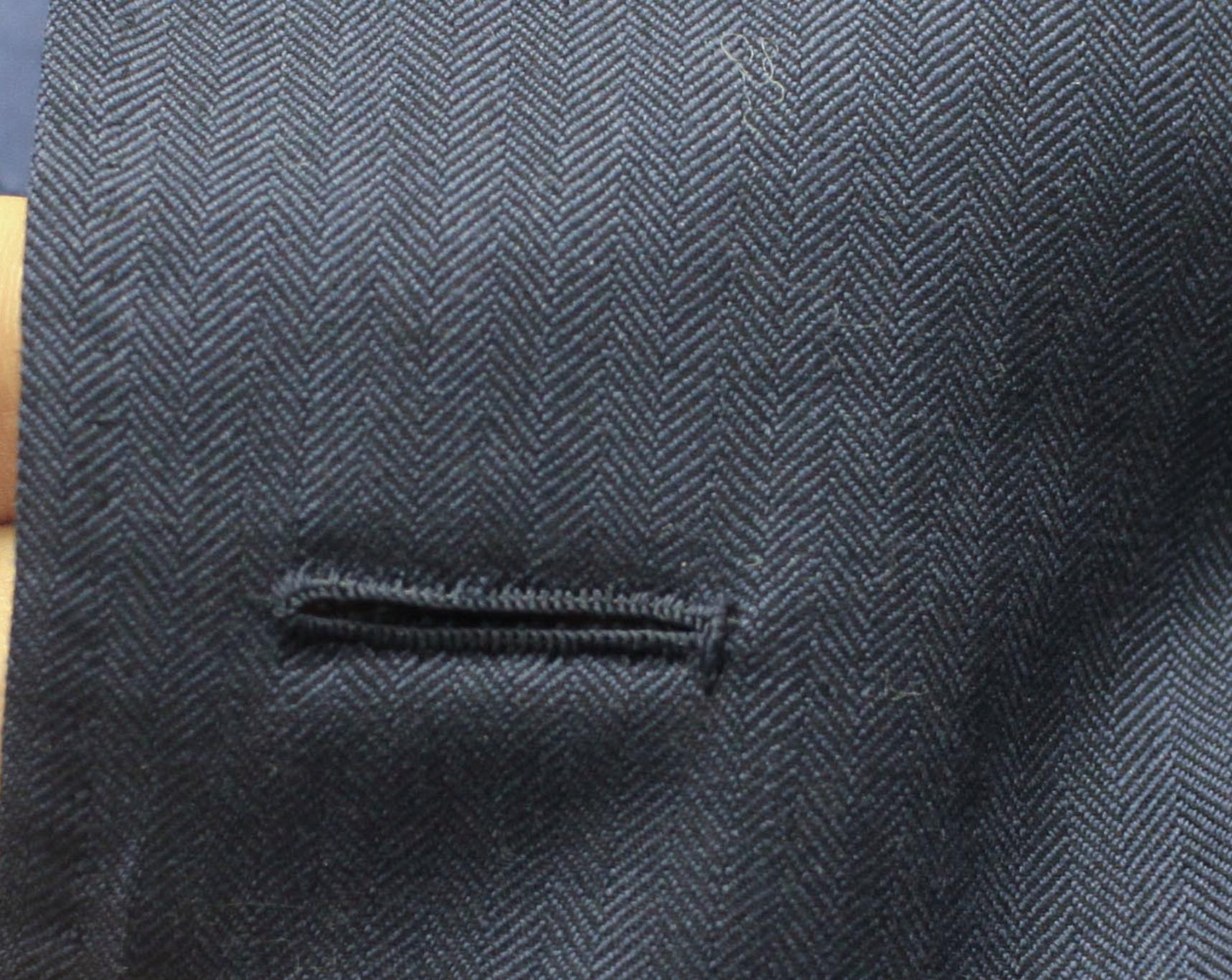 Plutôt que d'avoir la traditionnelle forme en trou de serrure la boutonnière du bas est droite, un détail qui sert à rappeler que le bouton du bas doit toujours être laissé ouvert. (source: j.diduch)