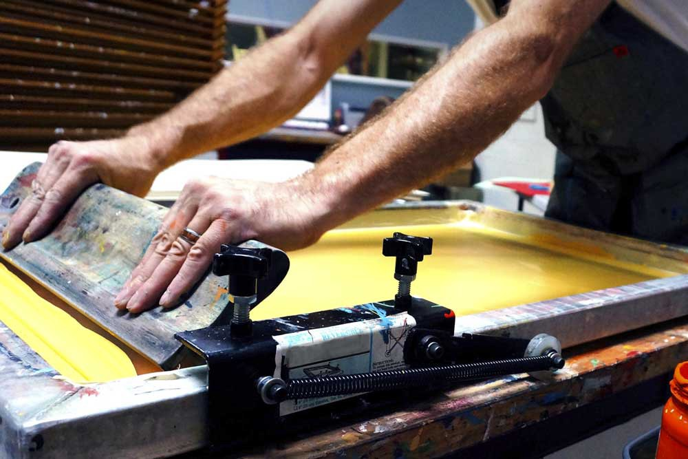 Un ouvrier forçant la couleur à travers l'écran à l'aide d'une raclette. (Source: Medium)